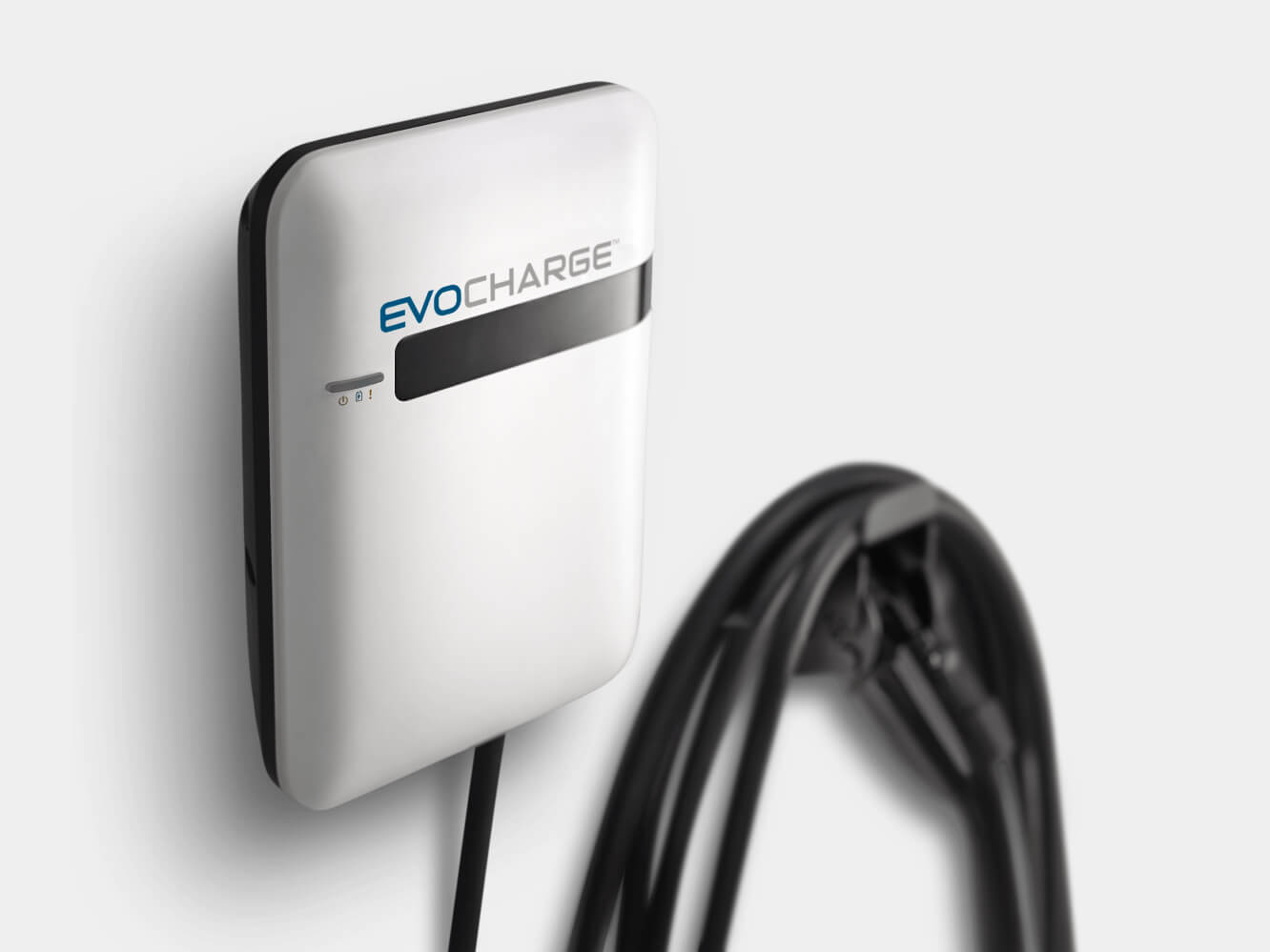 An EvoCharge charger hung up on a white wall