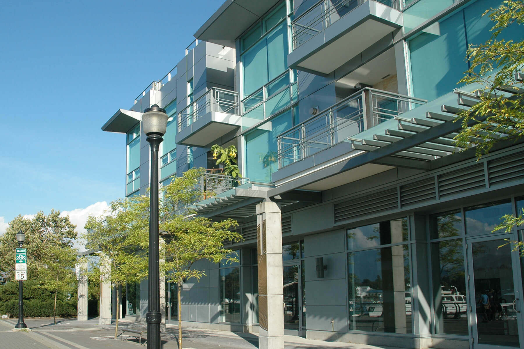 The outside of a glass apartment building with grey trim