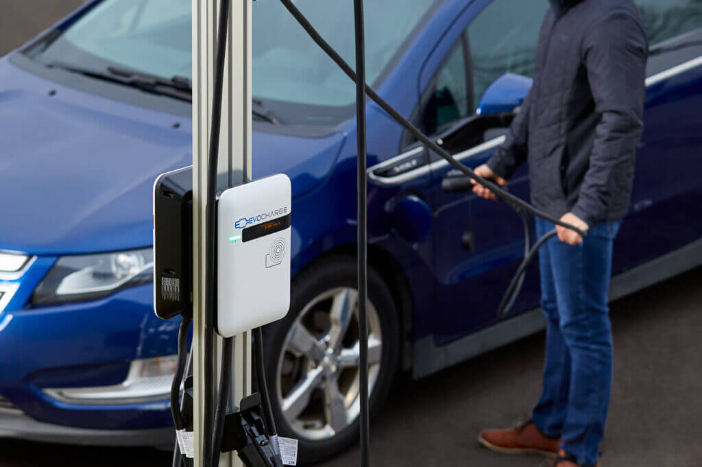 An EvoCharge charger in the forefront with a man charging his car in the background