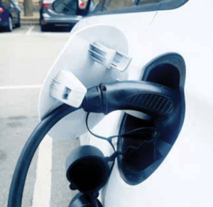 An electric charger sitting in the charging port of a white electric car