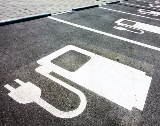 A parking space with a white symbol that represents an electric car charging station