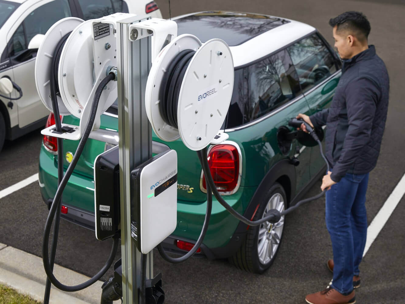A man charging his green mini cooper with an EvoReel and EvoCharge charger