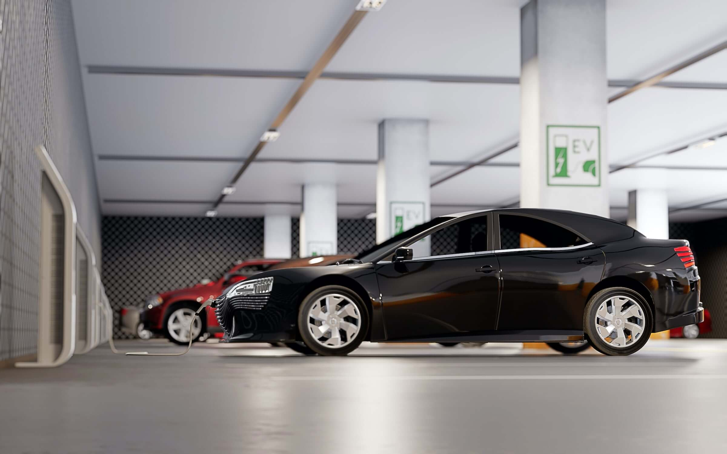 A black car in a parking garage being charged by an electric charger