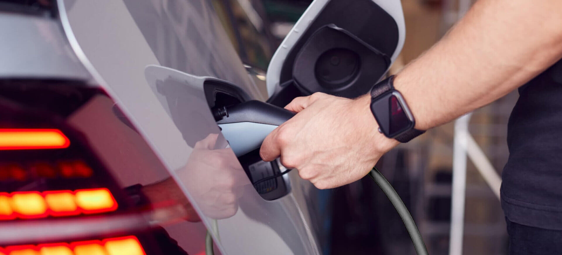 A man's hand inserting an electric charger into the charging port of his car