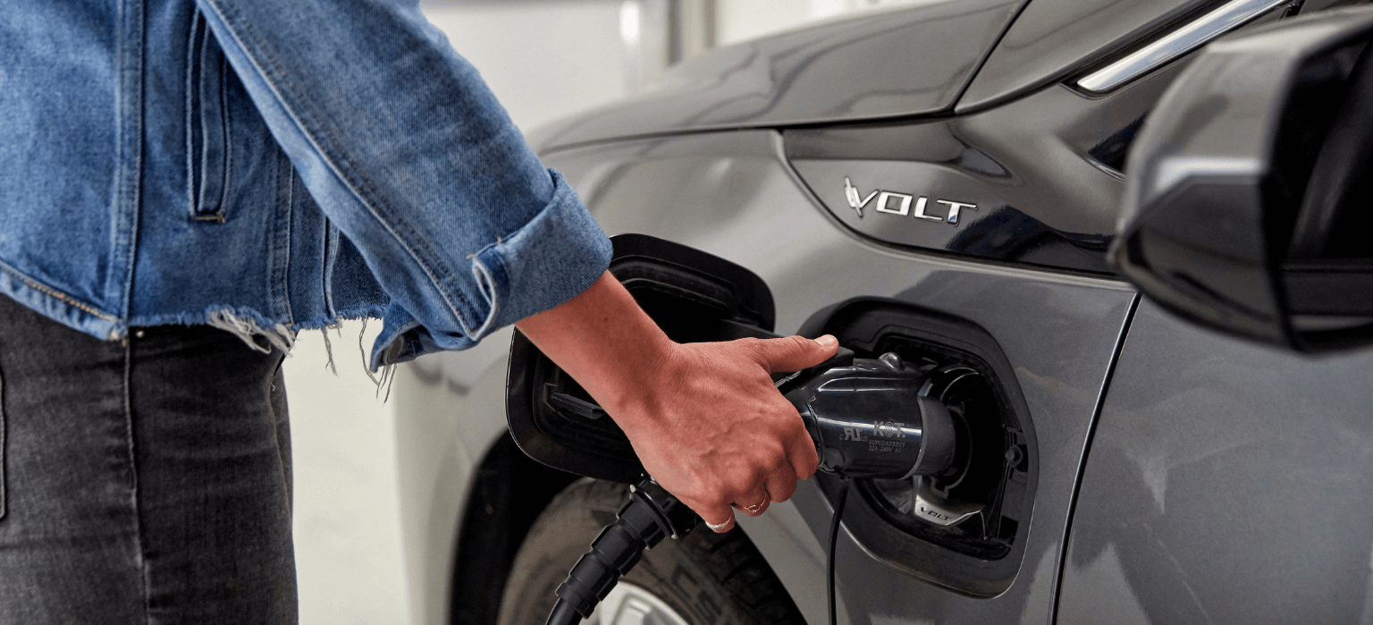 Woman's hand plugging charger into EV.