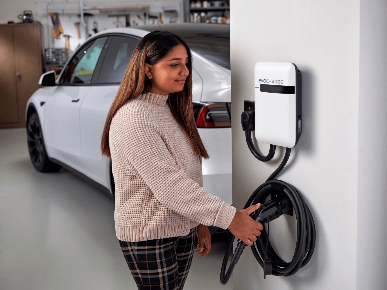 A woman in a garage grabbing charging handle of EvoCharge charger.